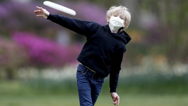 Shawn Cotter, 11, wears a face mask to protect against coronavirus, as he throws a Frisbee while playing catch with his father at Sherwood Gardens, Tuesday, April 21, 2020, in Baltimore.