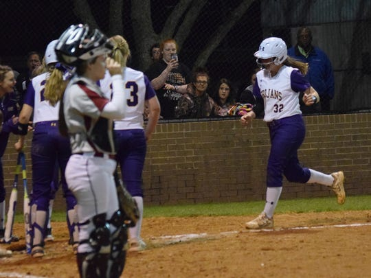 ASH's Carrie Boswell (32, right) heads for home plate