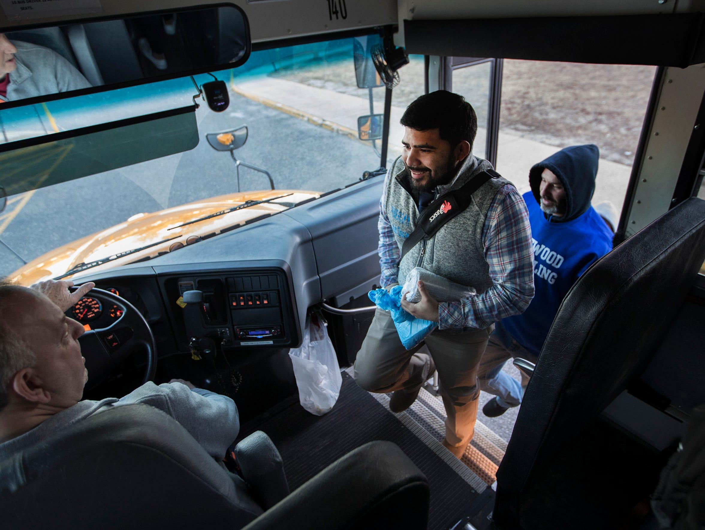 Lakewood Coach Oscar Orellana and team board bus for