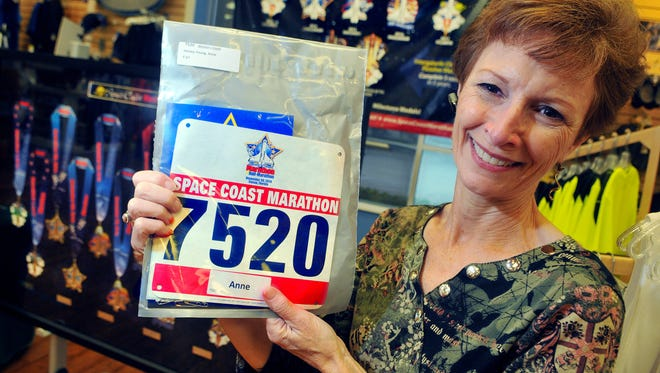 Anne Young, 67, of Indian Harbour Beach, picks up her race packet and number Tuesday afternoon at the Running Zone in Melbourne as she gets ready to run her 14th marathon at the upcoming Space Coast Marathon.