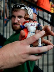 Baseball fans examine a Noah Syndergaard as Thor bobblehead doll before a baseball game between the New York Mets and the Oakland Athletics, Saturday, July 22, 2017, in New York. Bobblehead dolls were handed out to the first 15,000 fans attending the game.