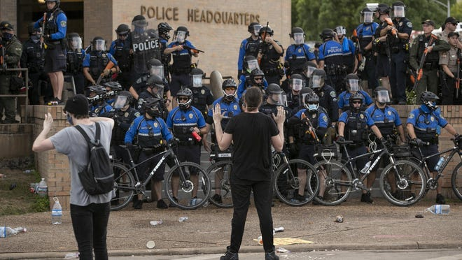 Austin police officers use bicycles to block the entrance to the Austin Police Department Headquarters building during protests against racism on May 30.