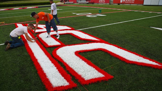 Members of the Turf Dogs crew lay out and make sure measurements are correct for installing the new ACC logo on to the field at Papa John's Cardinal Stadium on June 24, 2014.