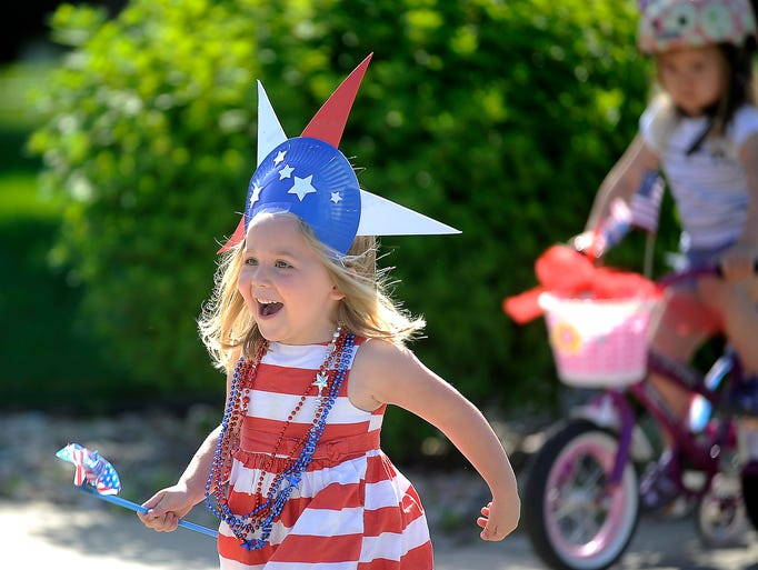 Mariah Schaefer takes part in the bike parade to Edgewood Prairie Crossing Assisted Living with Cindy's Daycare in Sioux Falls, S.D., Thursday, July, 3, 2014.