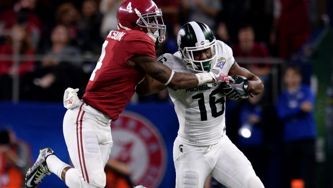 Spartan receiver Aaron Burbridge (16) stiff arms Alabama's Eddie Jackson (4) to try and stay in bounds during Alabama's 38-0 win over Michigan State in the 80th Annual Cotton Bowl Classic Thursday, December 30, 2015 in Arlington, Texas.