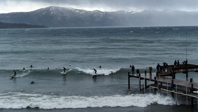 People watch from a pier as surfers catch some waves during a significant storm swell at Agate Bay near Kings Beach, Calif. on the shores of Lake Tahoe on Dec. 11, 2014.