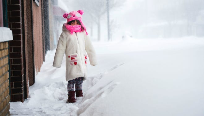 Erin Wu, 5, plays in the snow outside China Doll on Washington Avenue in Endicott on Tuesday afternoon.