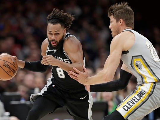 San Antonio Spurs' Patty Mills (8) is fouled by Cleveland Cavaliers' Kyle Korver (26) in the first half of an NBA basketball game, Sunday, Feb. 25, 2018, in Cleveland. (AP Photo/Tony Dejak)