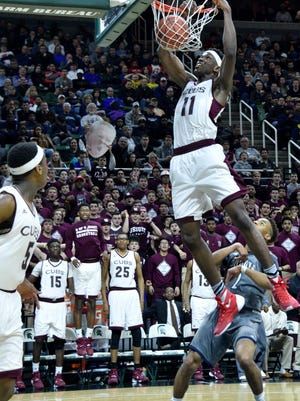 Jesuit's Gregory Egoigbodin (11) slams the ball through the basket on a feed from Cassius Winston (left) as Detroit U-D Jesuit beats Macomb Dakota, 72-51, Friday in the Class A semifinals at Breslin Center.