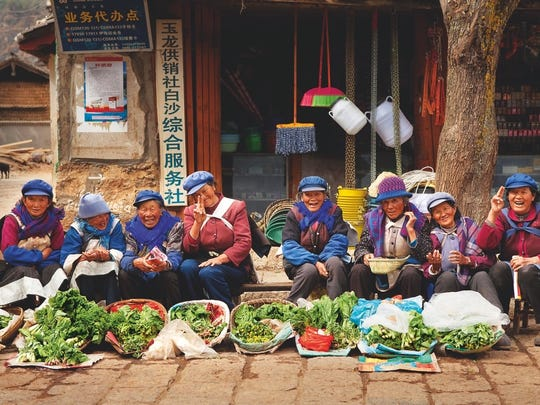 Naxi villagers in China sell fresh veggies.