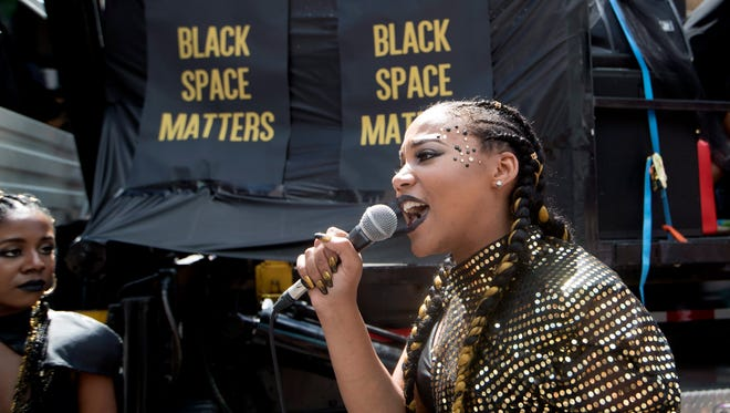 A member of the Black Lives Matters movement speaks to members as they stage a sit-in in Toronto on July 3, 2016.