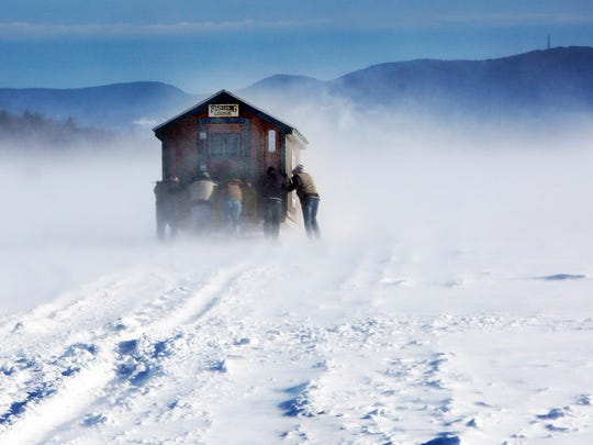 A gust of wind whips up snow as a group of ice fishermen