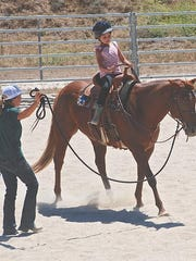 Thalia Jacobs, 9, takes a ride on one of the Hope Horses & Kids horses. Leading the horse is instructor Ashley Pollacci.