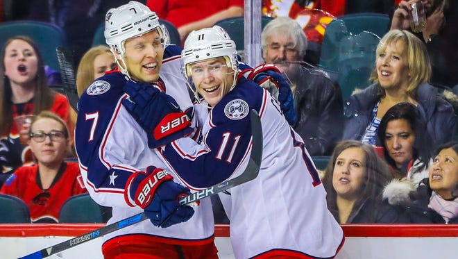 Blue Jackets forward Matt Calvert (11) celebrates his goal with defenseman Jack Johnson (7).