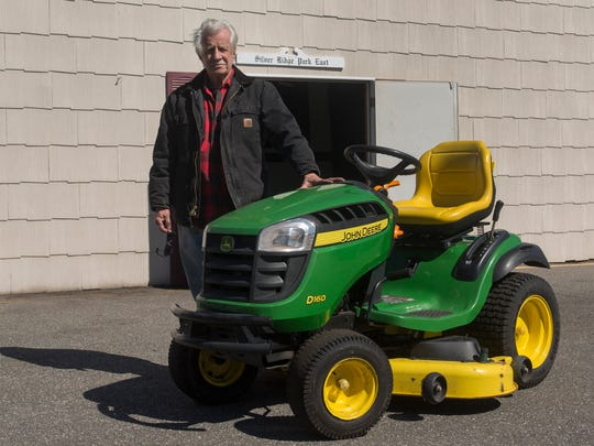 Bill Kollien of the Silver Ridge Park Association stands with the John Deere tractor that has finally been fixed, for free, after Press on Your Side stepped in.