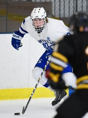 Sartell's Spencer Meier skates the puck past Warroad's