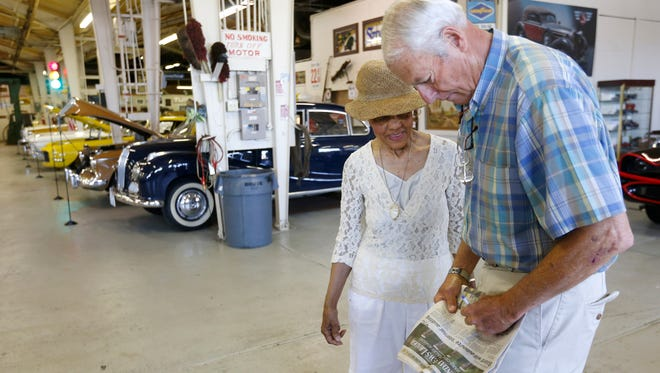 Route 66 Car Museum owner Guy Mace signs a newspaper article for Elaine Graham Estes, his first customer, on Wednesday, June 15, 2016.