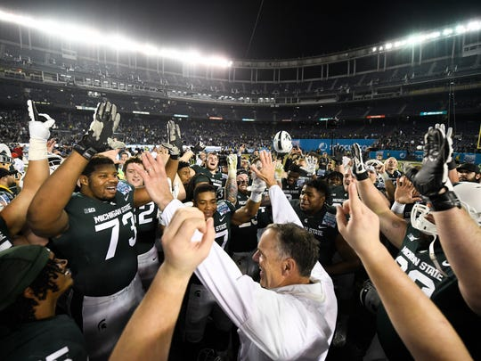 Michigan State coach Mark Dantonio, center, celebrates