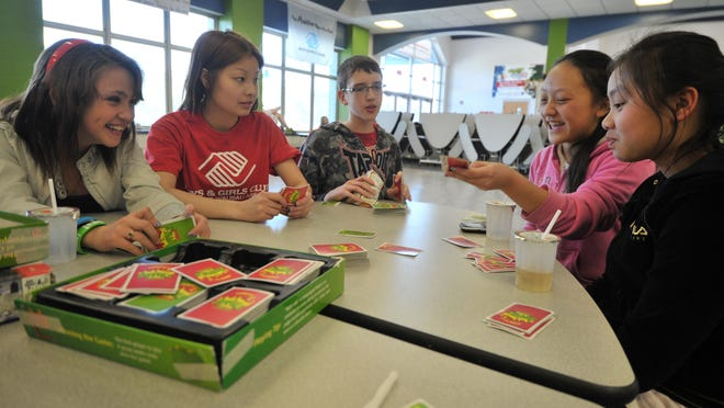 Gina Lomio, from left, Boys & Girls Club of the Wausau Area staff member Choua Lor, Caleb Merrick, Yingyee Xiong and Kao Moua play a card game in 2012 at D.C. Everest Middle School.