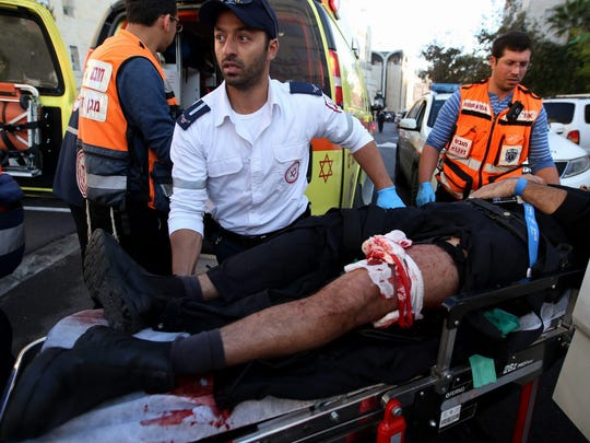A wounded Israeli man is taken to an ambulance after his leg was bandaged at the scene of an attack at a synagogue in Jerusalem on Nov.18.