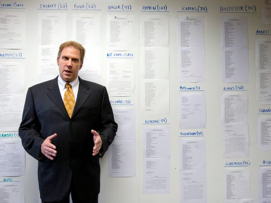 Lawyer Craig Mitnick speaks as he stands for a photograph Friday, July 18, 2014, in Haddonfield, N.J., in front of lists of some of the approximate 1,400 players in NFL concussion litigation he represents.  Under a tentative class-action settlement, the NFL would pay at least $765 million to compensate nearly 20,000 retired players over 65 years. (AP Photo/Matt Rourke)
