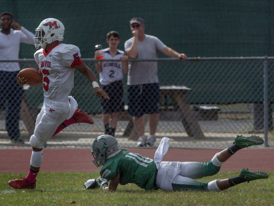 Manalapan's Naim Mayfield outruns the grasp of Colts Neck's Alajah Dawson to score one of his team's first half touchdowns.  Manalapan Football vs Colts Neck in Colts Neck, NJ on October 7, 2017.