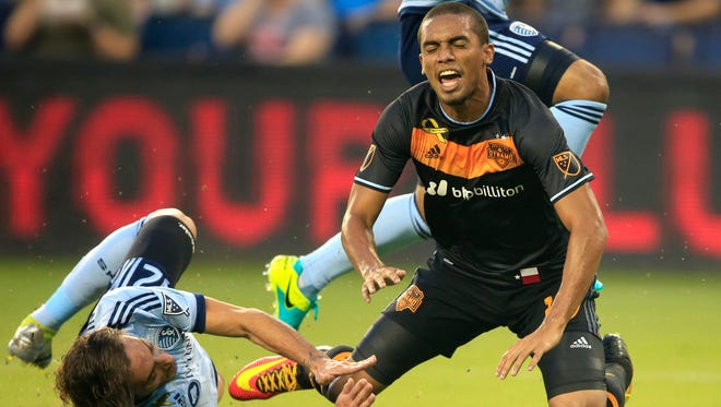 Sporting Kansas City defender Nuno Coelho (12) and Houston Dynamo forward Mauro Manotas (19) during the first half of an MLS soccer match in Kansas City, Kan., Friday, Sept. 9, 2016.