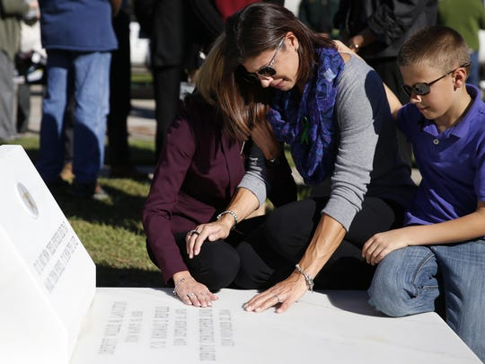 Widow Erika Slizewski-Smith touches the memorial for her late husband Deputy Chris Smith with their son Hunter, 11, at her side at the Leon County Sheriff's Office after its unveiling during a ceremony on Friday.