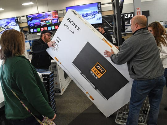 Mike Looper, left, of Pickens loads a cart with a $1,200 70-inch television during Black Friday at the Best Buy on Woodruff Road in Greenville.