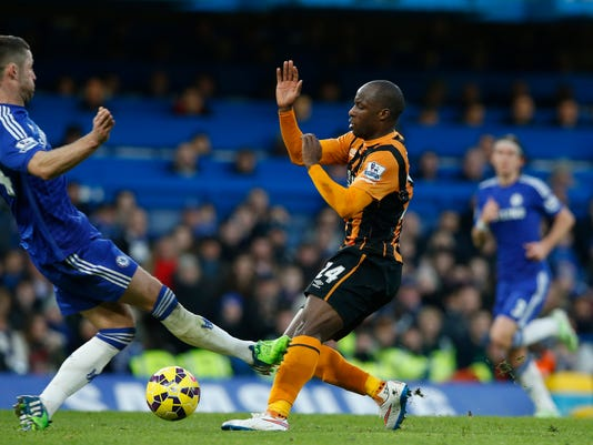 Chelsea's Gary Cahill, left puts up a foot as he tackles Hull's Sone Aluko for which he was shown a yellow card by referee Chris Foy, during their English Premier League soccer match between Chelsea and Hull City at Stamford Bridge stadium in London, Saturday, Dec 13, 2014. (AP Photo/Alastair Grant)