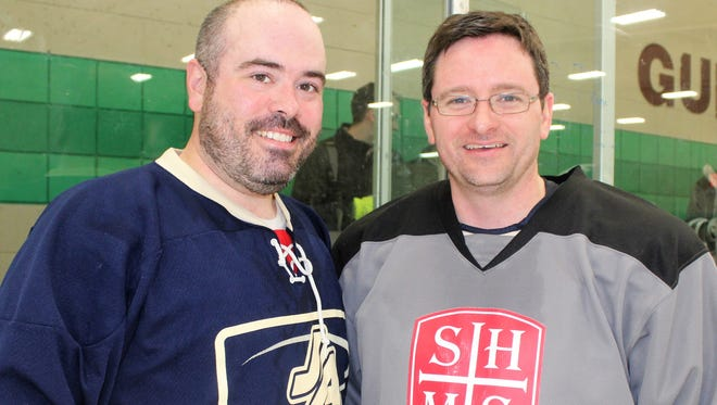 The Rev. Paul Graney  (left), associate pastor of Our Lady of Sorrows, and Deacon Mark Livingston were on opposite sides during Friday's recreational ice hockey game at the Farmington Hills Ice Arena.