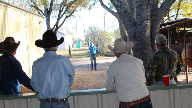 Charlie Roland Jr. tosses a horseshoe under watchful eyes of a standing room only-crowd outside the Blackwell Volunteer Fire Department hall. Roland teamed with Will Steinbach to win the match. Spectators were not required to wear cowboy hats, but they did.