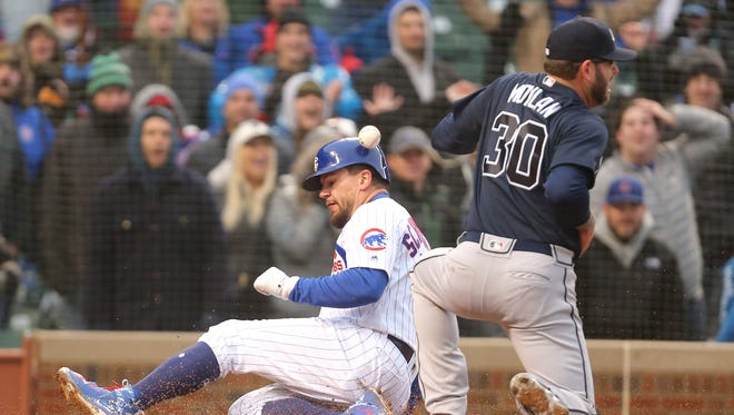 Chicago Cubs left fielder Kyle Schwarber (12) scores a run with Atlanta Braves relief pitcher Peter Moylan (30) attempting the tag during the eighth inning at Wrigley Field.