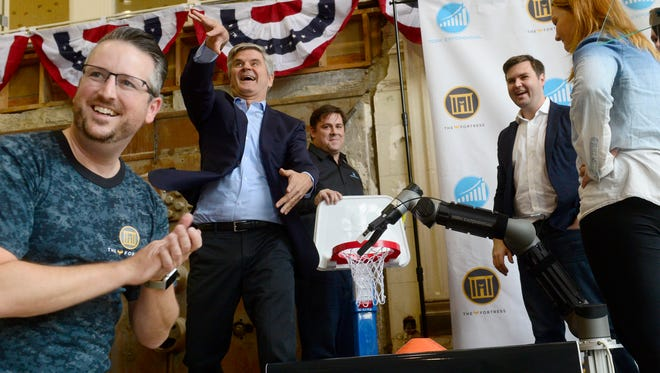 Steve Case, second from left, throws a ball into the crowd after students demonstrated their robot's ability to dunk the ball into a basket. Case, along with J.D. Vance, second from right, visited the Fortress Academy in York on Tuesday, Oct. 10, 2017, during the Rise of the Rest tour. The purpose of the tour is to bring attention to startups in areas of the country that don't get a lot of attention from venture capitalists.