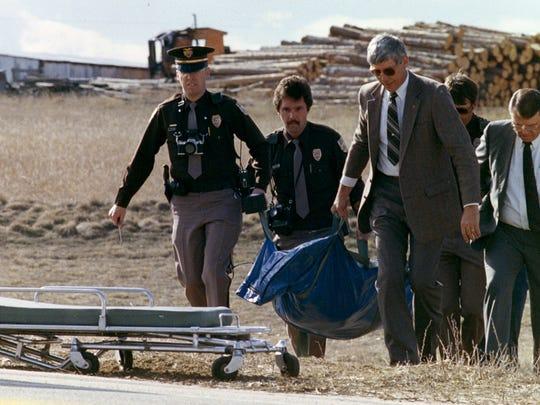 Police investigators move the body of Peggy Lee Hettrick
