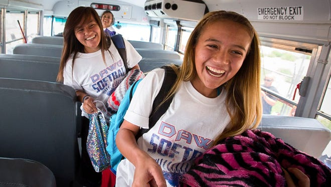 Las Cruces High School softball players 16-year-old 10th-grader Brandy Lozoya, left, and 14-year-old 9th-grader Samantha Lopez board a bus to take them to Rio Rancho for the Class 6A tournament, May 11, 2016.