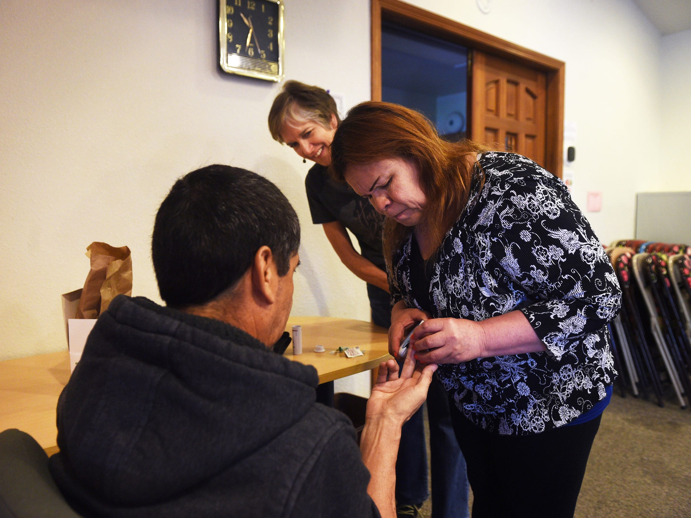 David Chavez-Macias, left, gets his blood drawn by his wife Leticia Guillen while under the watchful eye of Nurse Practitioner Brooke Walker at the Unitarian Universalist Fellowship of Northern Nevada in Reno on May 16, 2017. Chavez-Macias has been granted sanctuary by the church after being issued deportation orders by U.S. Immigration and Customs Enforcement, or ICE.