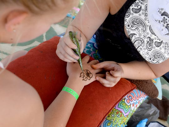 A customer gets a henna tattoo at Red Leaf Henna booth.