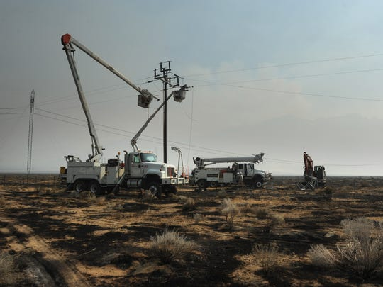Crews work to repair burned power lines along State Route 447 following a wildfire on the way to Burning Man near Gerlach, Nevada on Aug. 31, 2017.