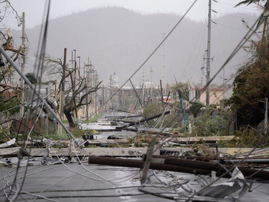 Electricity poles and lines lay toppled on the road after Hurricane Maria hit Puerto Rico.