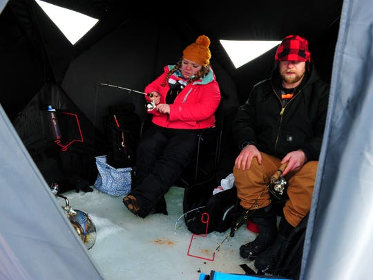 "Elizabeth Reed and Alex Krier ice fish on Holter Lake, Wednesday. ""I love it,"" Krier said."