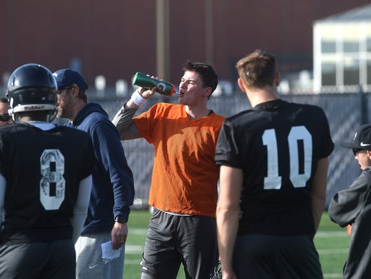 Nevada quarterback Carson Strong grabs a drink during