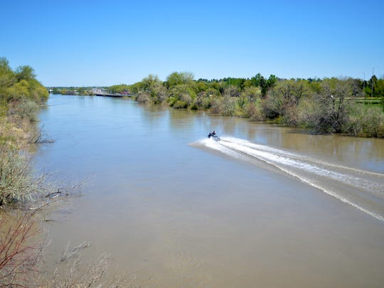 A jet skier rides down the Sun River towards the confluence