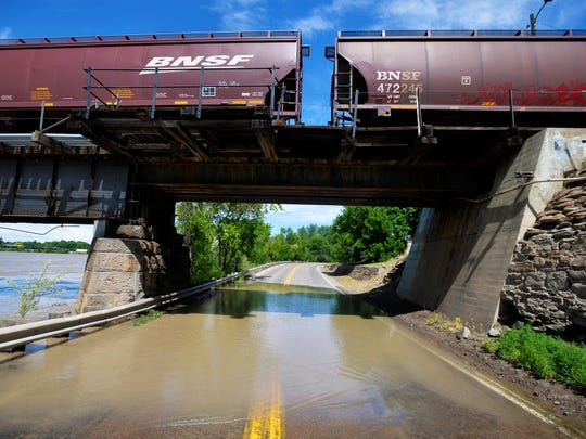 Missouri River floods at River Drive South under the train overpass, Thursday.
