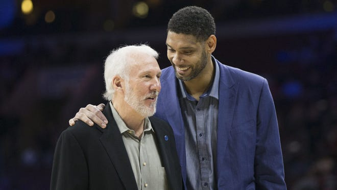 In a file photo, scratched San Antonio Spurs center Tim Duncan (R) dressed in plain clothes talks with head coach Gregg Popovich during the first quarter at Wells Fargo Center.