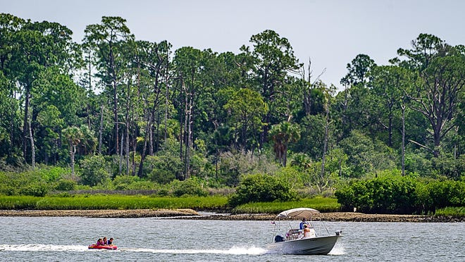 A powerboat pulling children on a raft travels south on the Matanzas River past the Fish Island property in St. Augustine on Thursday.