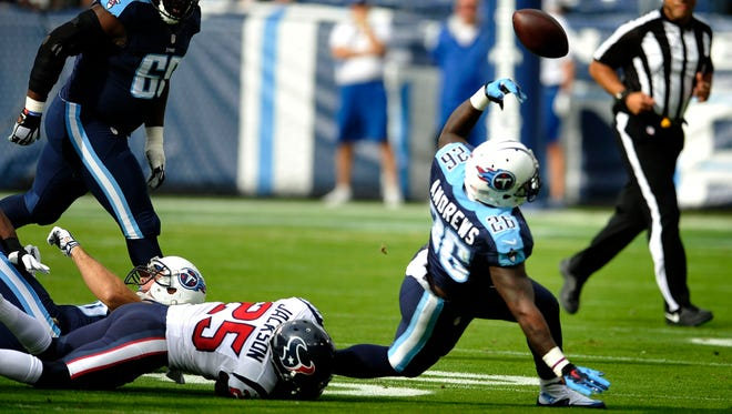 Titans running back Antonio Andrews (26) fumbles the ball on the first offensive play of the game. The ball was recovered and taken in for a Texans touchdown.