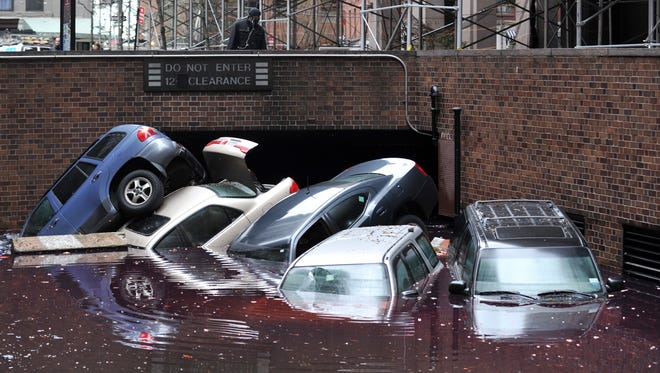 Cars piled on top of each other at the entrance to a garage on South Willliam Street in Lower Manhattan on Oct. 31, 2012, in New York as the city begins to clean up after Hurricane Sandy.