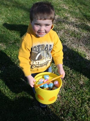 Tre Goodman, 3, shows off his haul during the annual Easter Egg Hunt held by the Clarksville Parks Department at Colgate Park on Saturday.