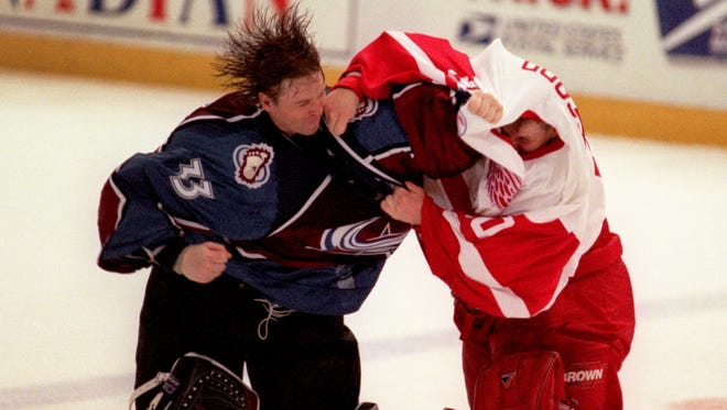 Red Wings goalie Chris Osgood and Colorado Avalanche's goalie Patrick Roy fight near center ice in the 3rd period Wednesday, April 1, 1998, at Joe Louis Arena.